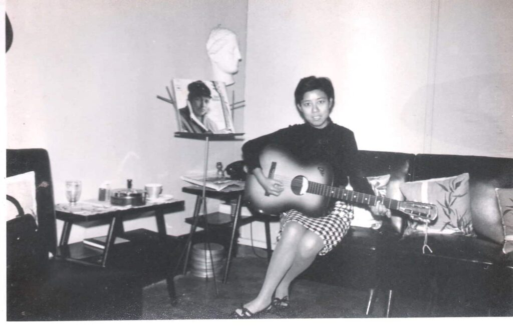Xi Xi playing guitar in the 1960's