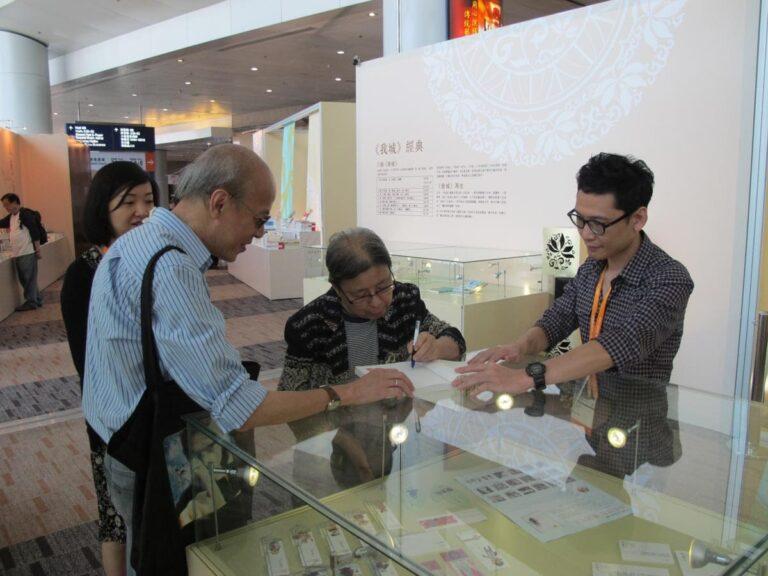 Xi Xi signs a book. at the Hong Kong Book Fair 2011